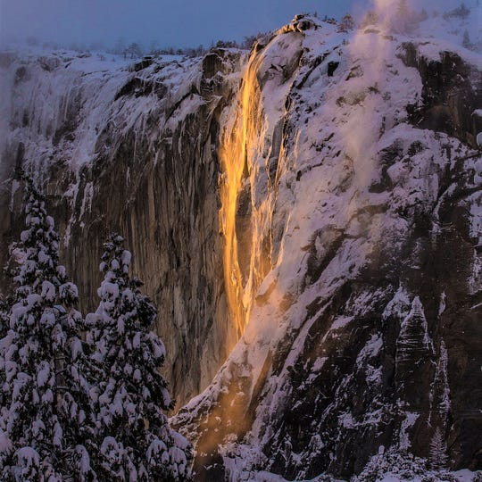 "This Sunday photo released by Dakota Snider shows Horsetail Fall in Yosemite National Park. The park is again wowing visitors and photographers with its annual ""firefall."" Every February for a few days, the setting sun illuminates the Horsetail Fall to make it glow like a cascade of molten lava."