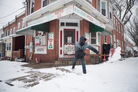 Tory Kellam shovels snow in front of Bernie's Original Italian Water Ice Wednesday afternoon in Wilmington. Kellam said he was shoveling the sidewalk as a courtesy to the neighborhood he's trying to build clientele in.