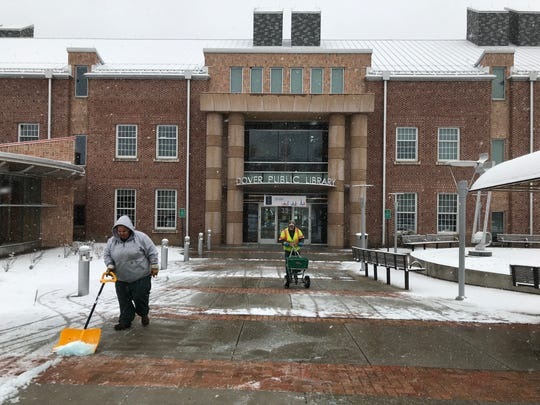A City of Dover public works employee shovels snow at the Dover Public Library in February.