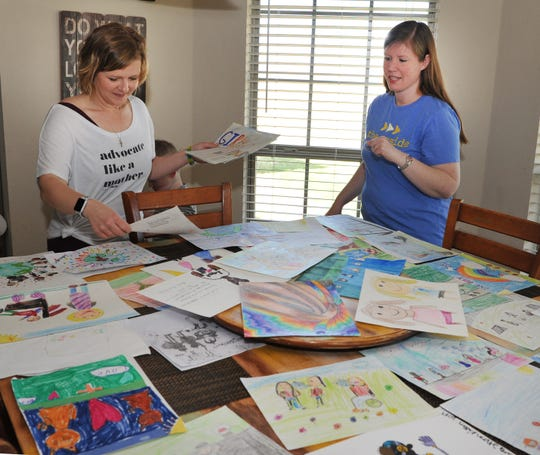 Misti Brock, left, and Kristin Crumb sort through artwork made by local school kids that were asked to make drawings on how to accept others with differences. The artwork is part of a contest that will be used to raise money that will be used to build an inclusive playground in Wichita Falls.
