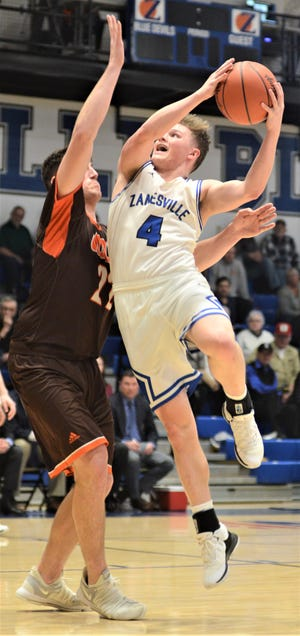 Zanesville's Clayton Foreman drives against Meadowbrook's Davis Black in Tuesday's 56-35 loss at Winland Memorial Gymnasium.