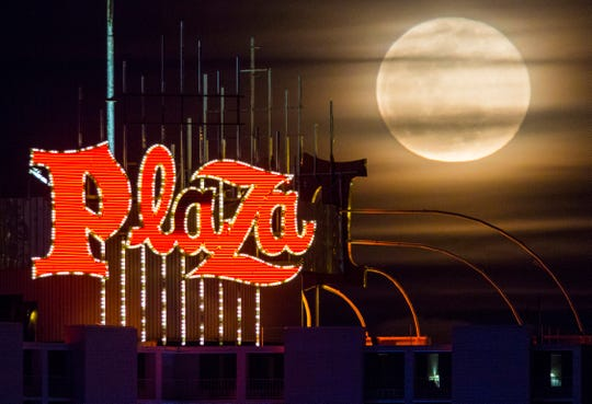 A super snow moon rises over the Plaza Hotel and Casino in downtown Las Vegas on Tuesday.
