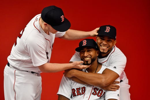 Brock Holt helps Eduardo Nunez and shortstop Xander Bogaerts as they pose.