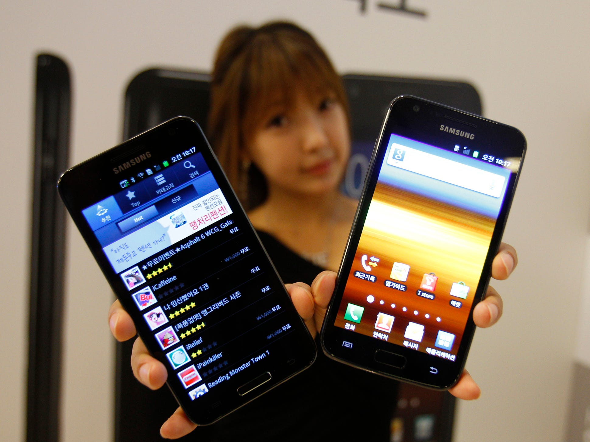 A model poses with Samsung Electronics' new smart phones Galaxy S II LTE, right, which features the 4.5-inch Super Amoled Plus screen and runs on Android 2.3, and Galaxy S II HD LTE, which features the 4.65 HD Super Amoled screen, during its unveiling ceremony in Seoul, South Korea, Monday, Sept. 26, 2011. The non-4G LTE Galaxy S II had a 4.3-inch display.