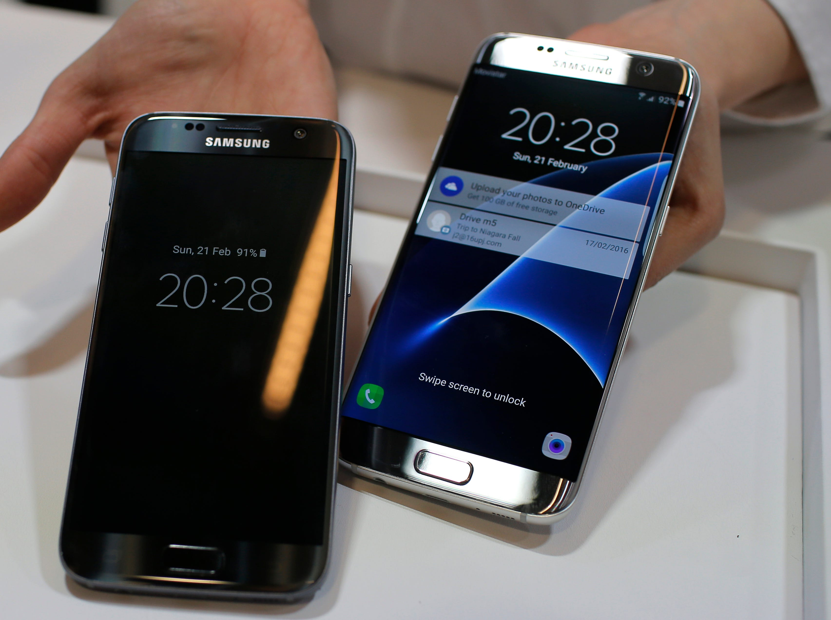 In this Sunday, Feb. 21, 2016, file photo, a Samsung Galaxy S7, left, and S7 Edge are displayed during the Samsung Galaxy Unpacked 2016 event. The new Galaxy S7 and S7 Edge phones take better pictures than the S6 models and brought back popular features such as water resistance and a microSD card slot.