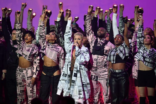 Pink, center front, performs at the Brit Awards Wednesday in London, where she received an award for her contribution to music.