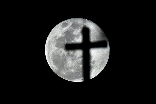 A cross is silhouetted against the full Moon in the Mexico City sky on Feb. 19.