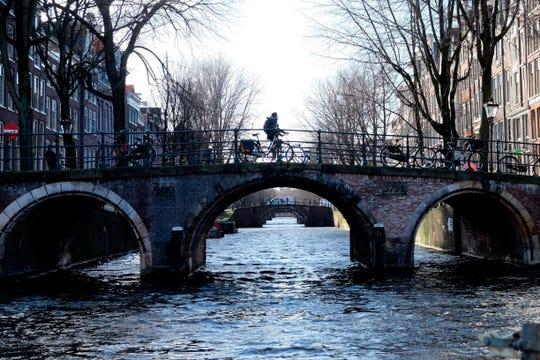 A cyclist pedals over a bridge over the Leidsegracht canal in Amsterdam, Thursday, Feb. 7, 2019.  Amsterdam's city hall says that kilometers (miles) of walls along its world famous canals are crumbling and in urgent need of repair following years of neglect. (AP Photo/Michael Corder) ORG XMIT: AMB115