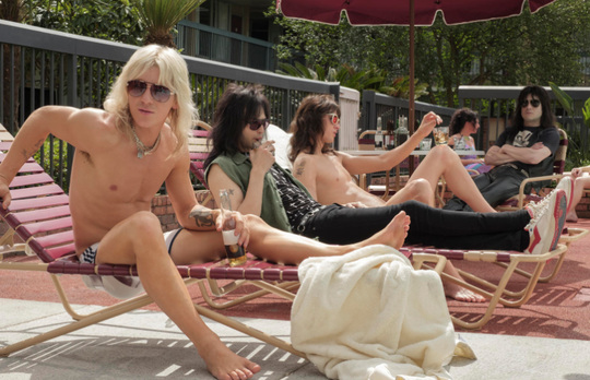 "Vince Neil (Daniel Webber, left), Nikki Sixx (Douglas Booth), Tommy Lee (Colson Baker) and Mick Mars (Iwan Rheon) hang out by the pool in Netflix's Motley Crue biopic ""The Dirt."""