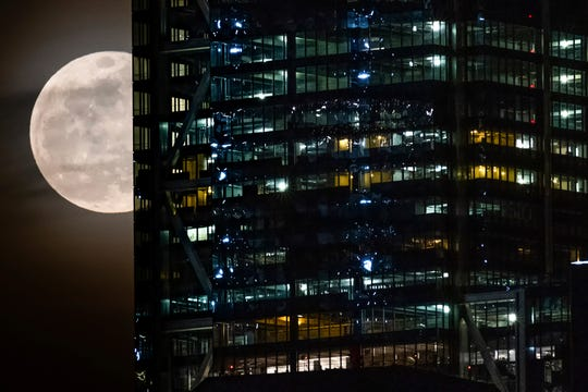 The supermoon passes behind the World Trade Center in New York City on Tuesday.