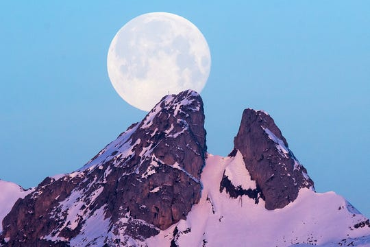 A view of the supermoon in the sky over the Les Jumelles Mountains in Plambuit, Switzerland.
