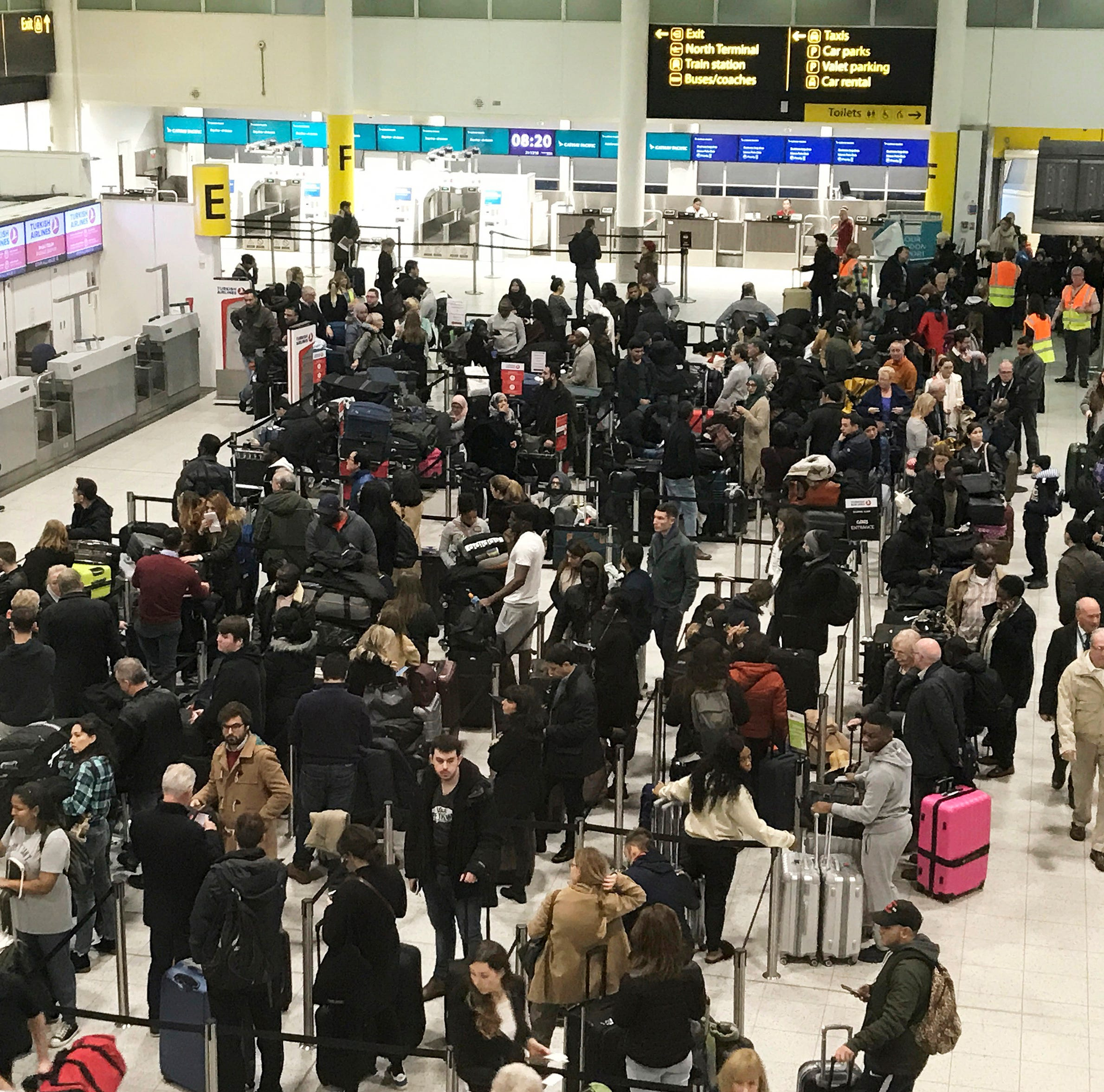 FILE - In this Dec. 21, 2018, file photo, passengers wait to check in at Gatwick Airport in England. Britain is extending the no-fly zone for drones around airports to 5 kilometers (3.1 miles) in an attempt to avert disruptions like the December groundings of flights at Gatwick Airport. (AP Photo/Kirsty Wigglesworth, File) ORG XMIT: NYHK202