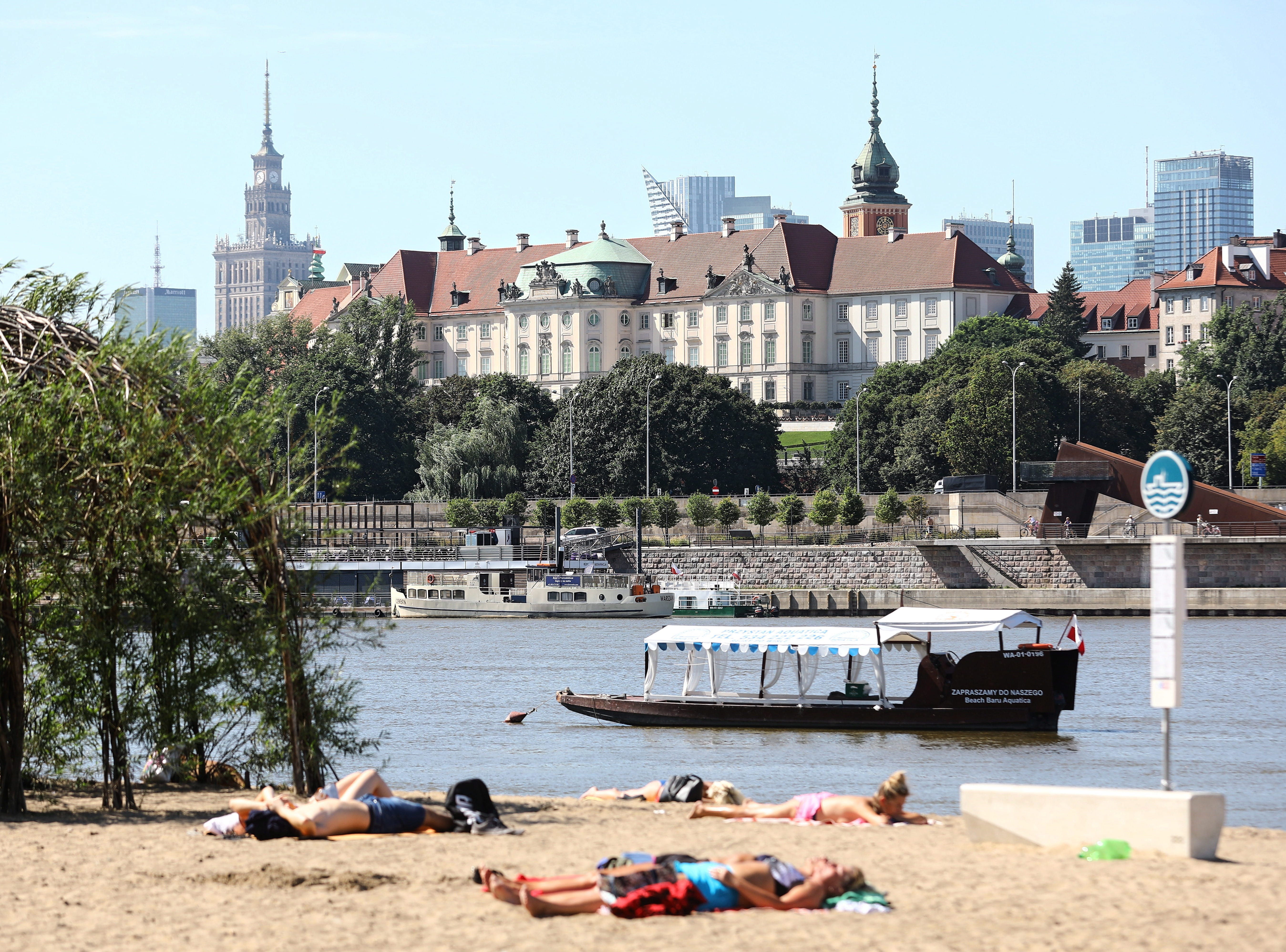 epa06935060 People enjoy a sunny and hot weather at a city beach on the Vistula river in Warsaw Poland, 08 Agust 2018. A spell of heat wave is going throughout Europe with temperatures up to 39 degrees Celsius.  EPA-EFE/RAFAL GUZ POLAND OUT