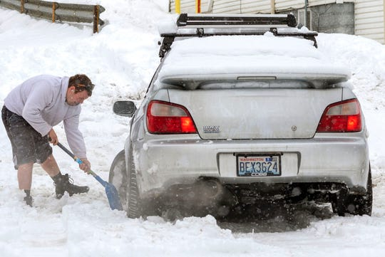An unidentified motorist works to get his stuck car out of his driveway on Wednesday, Feb. 13, 2019, during a snow storm in Pullman, Wash. (Geoff Crimmins/The Moscow-Pullman Daily News via AP)