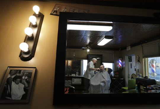With pictures of Elvis Presley scattered about the room, Ken Van De Wettering, 86, gives a haircut to Tim Gibson of Oshkosh at Greasy Fingers barbershop Thursday in Appleton.