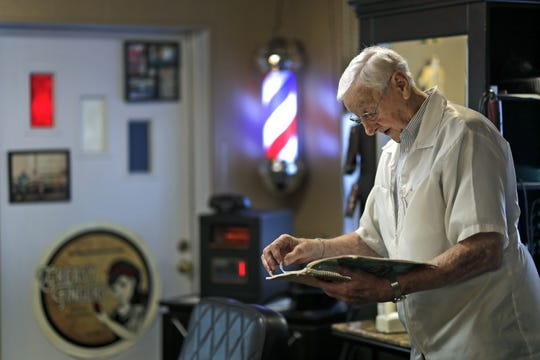 Barber Ken Van De Wettering looks over his appointment log as he waits for his first customer to arrive at Greasy Fingers barbershop Thursday in Appleton. The 86-year-old barber has been cutting hair since he was a teenager.