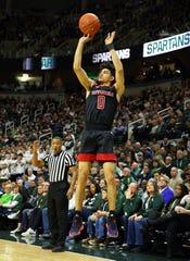 Feb 20, 2019; East Lansing, MI, USA; Rutgers Scarlet Knights guard Geo Baker (0) attempts a three point basket during the first half of a game against the Michigan State Spartans at the Breslin Center.