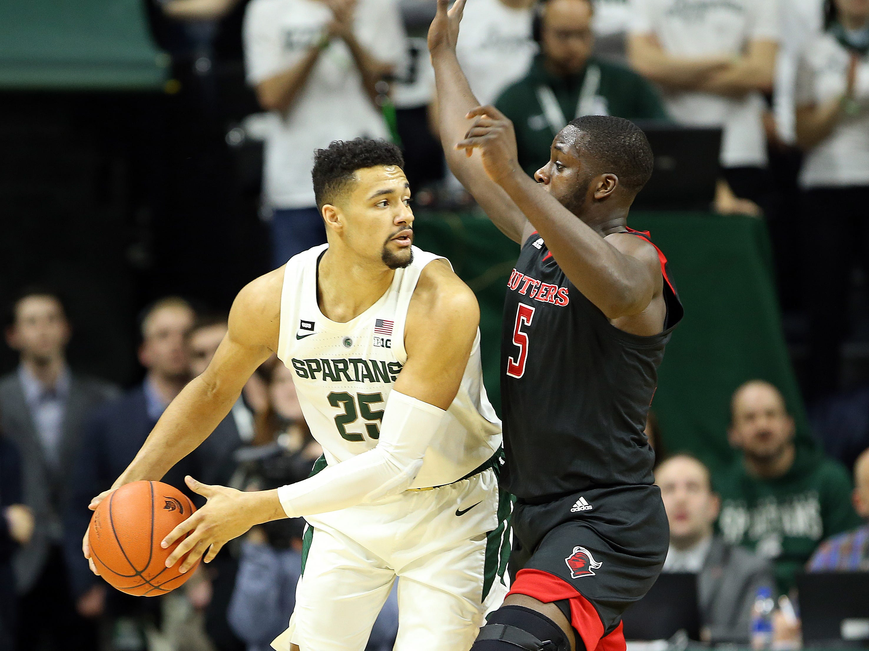 Feb 20, 2019; East Lansing, MI, USA; Michigan State Spartans forward Kenny Goins (25) is defended by Rutgers Scarlet Knights forward Eugene Omoruyi (5) during the first half of a game at the Breslin Center.