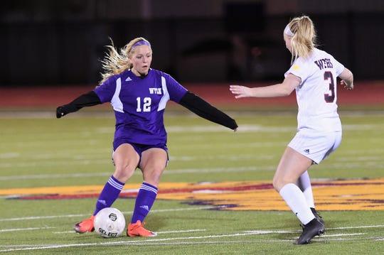 Wylie's Kaitlyn Via (12) tries to pass around Wichita Falls High's Ashby Hood (3) at Bulldog Stadium on Wednesday, Feb. 20, 2019.