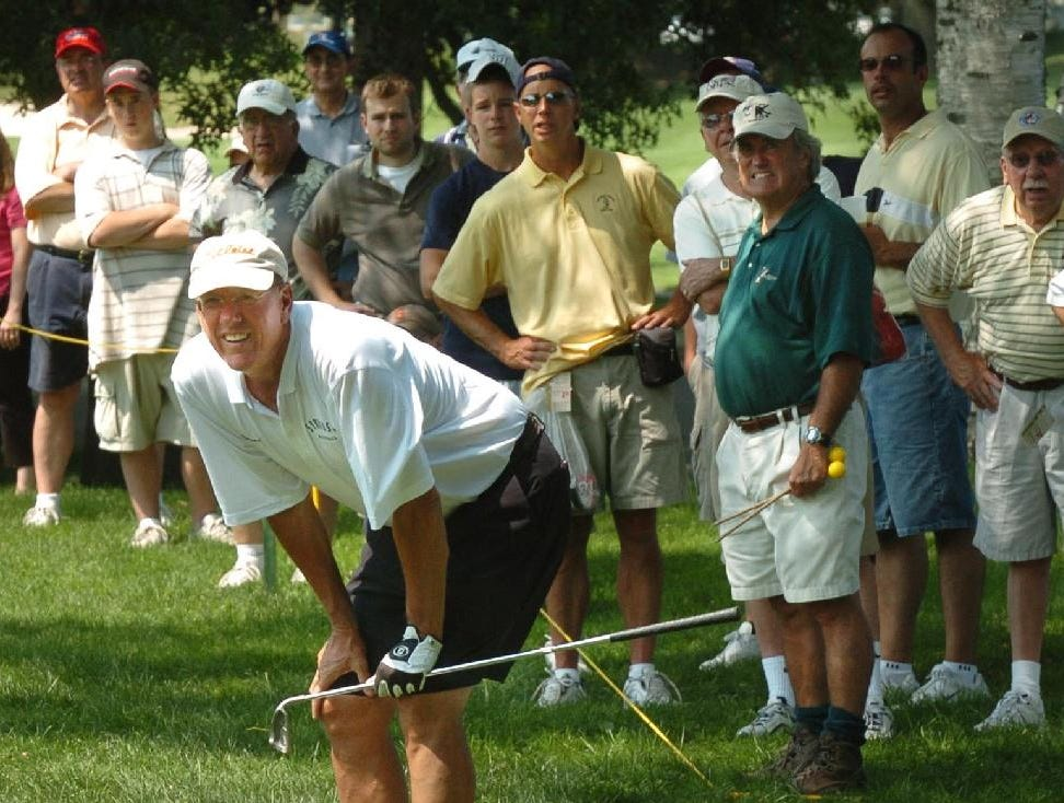 2005: Syracuse University basketball coach Jim Boeheim stoops to spot his fairway shot on the third hole as fans watch during Wednesday's Pro-Am tournament at En-Joie Golf Club in Endicott.