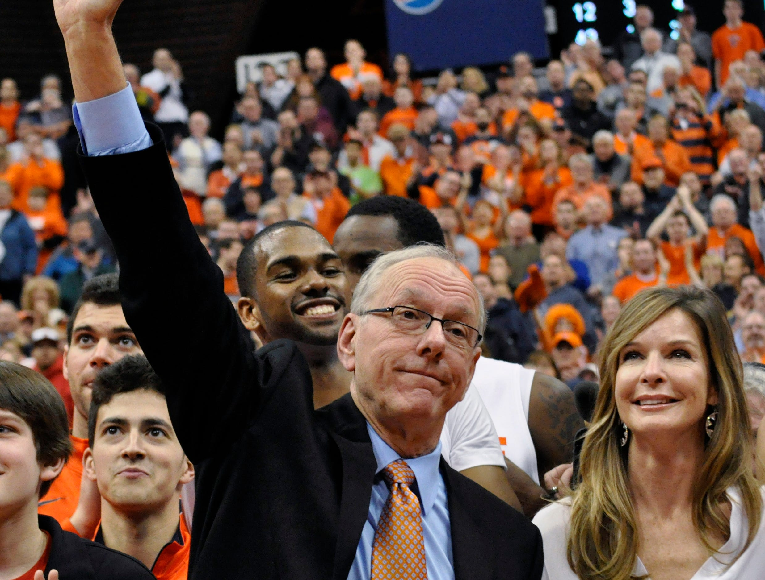2012: Syracuse coach Jim Boeheim, standing next to his wife, Julie, waves to the crowd after his 900th win, in Syracuse's 72-68 victory over Detroit in an NCAA college basketball game in Syracuse, N.Y., Monday, Dec. 17, 2012. (AP Photo/Kevin Rivoli)