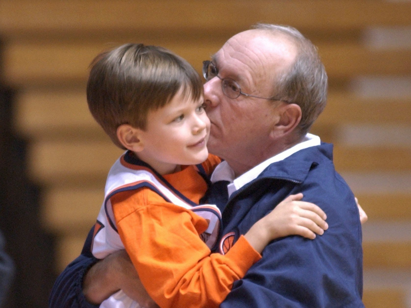 2003: Syracuse coach Jim Boeheim gives a hug and a kiss to his son Jim III at the end of media day in Syracuse, N.Y., Friday, Oct. 17, 2003.  (AP Photo/Kevin Rivoli)