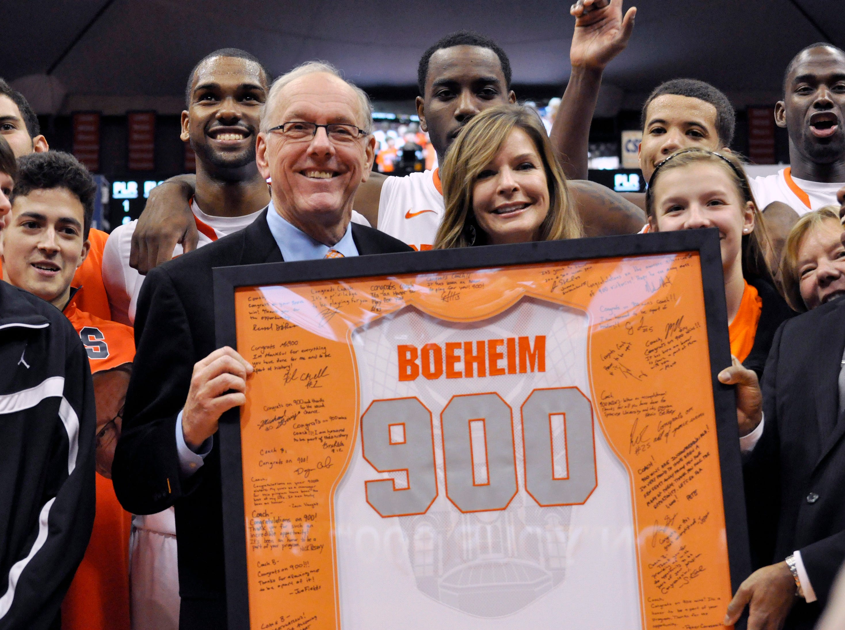2012: Syracuse coach Jim Boeheim, joined by his wife, Julie, is presented with a jersey for his 900th career win, after Syracuse defeated Detroit 72-68 in an NCAA college basketball game in Syracuse, N.Y., Monday, Dec. 17, 2012. (AP Photo/Kevin Rivoli)