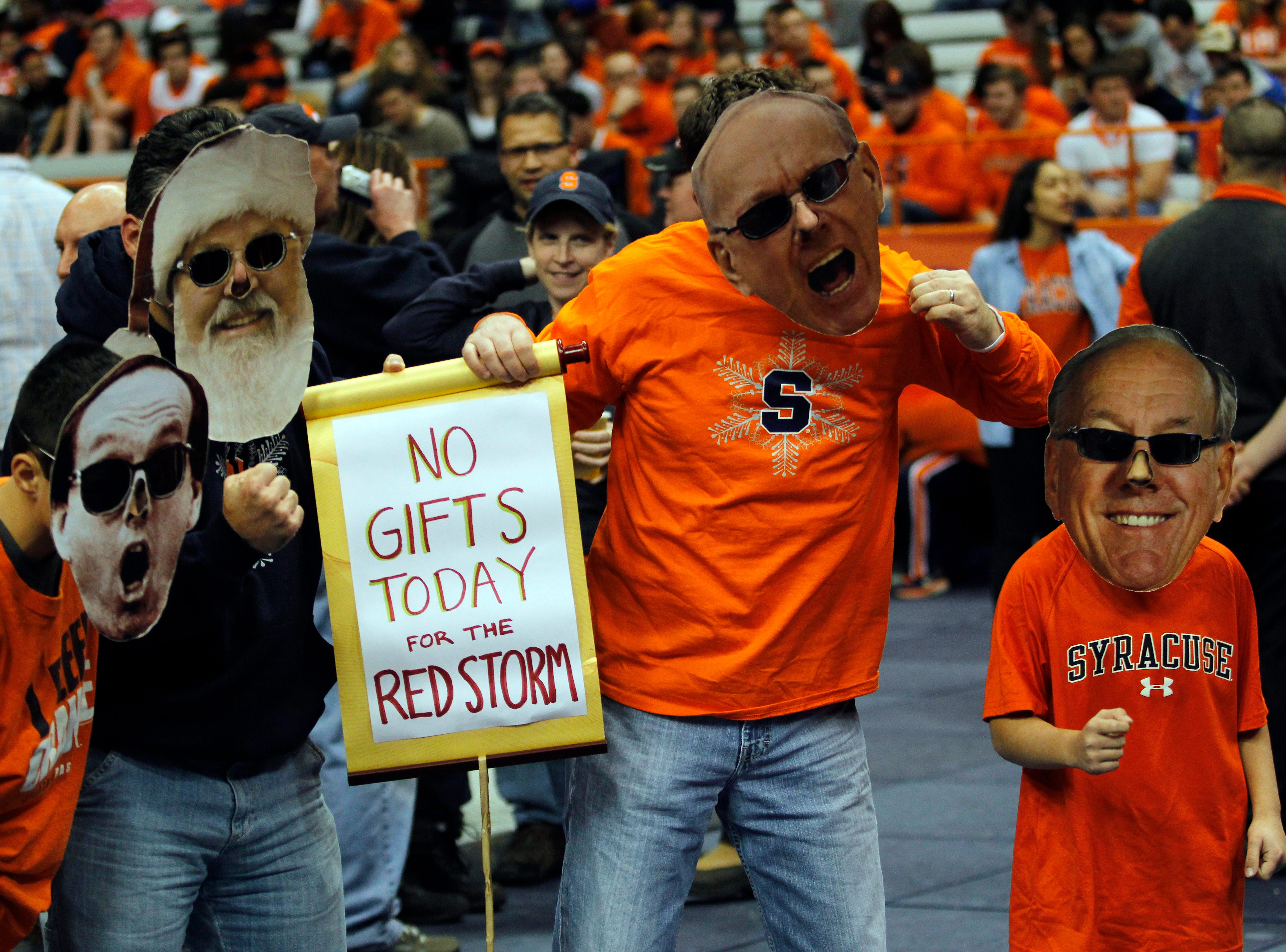 2014: Syracuse fans wearing masks of Syracuse head coach Jim Boeheim and Santa cheer at an NCAA college basketball game against St. John's in Syracuse, N.Y., Saturday, Dec. 6, 2014. (AP Photo/Nick Lisi)