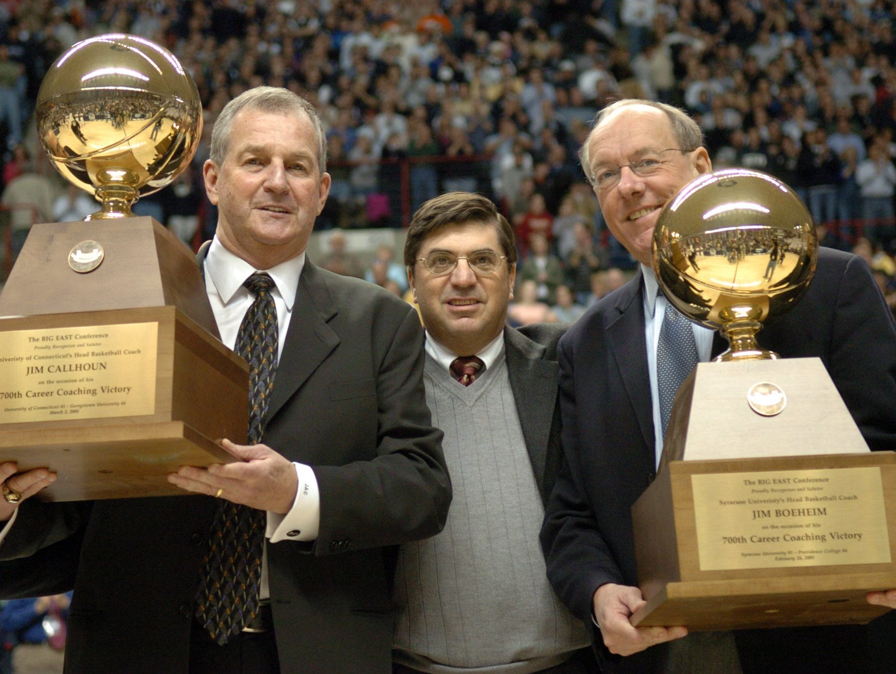 2005: Connecticut coach Jim Calhoun, left, and Syracuse coach Jim Boeheim, flank Big East Commissioner Mike Tranghese after they were presented with their trophies for coaches with 700 wins, before the start of a game in Storrs, Conn., in this March 5, 2005 photo. Boeheim and Calhoun were elected to the Basketball Hall of Fame on Monday April 4, 2005. (AP Photo/Steve Miller)