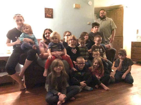 The Card family shown in the home they're renting in Glen Aubrey after their home was destroyed in a November 2017 fire. From left back row: Brianna, 18; Angela Card, Ella, 13; Justin, 10; Abram, 15; and Brian Card. From left center row: Sophia, 1; Ralphie, 2; Mariana, 7; Nicholas, 5; and James, 6. From left bottom row: Clare, 8; Dennis, 6; Annie, 3; Dominic, 5; and Joey, 9.