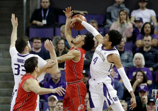 Washington's Matisse Thybulle (4) knocks the ball away from Utah's Sedrick Barefield as Washington's Sam Timmins (33) and Utah's Novak Topalovic watch during the first half of an NCAA college basketball game Wednesday, Feb. 20, 2019, in Seattle.