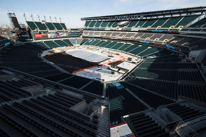 Workers prepare Lincoln Financial Field for the upcoming Stadium Series that is scheduled for Saturday night, weather permitting.