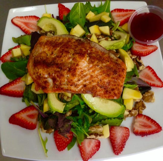A Salmon Avo Berry Salad features grilled salmon filet, arugula, goat cheese, strawberries, avocado, toasted almonds and a side of raspberry vinaigrette.