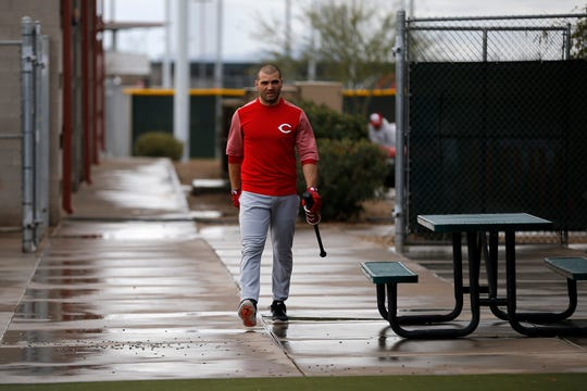 Cincinnati Reds first baseman Joey Votto (19) takes his bat under some shelter from the rain at the Cincinnati Reds spring training facility in Goodyear, Ariz., on Thursday, Feb. 21, 2019.