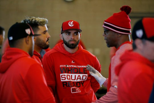 Cincinnati Reds third baseman Eugenio Suarez (7) and second baseman Jose Peraza (9) talk with first base coach Delino DeShields at the Cincinnati Reds spring training facility in Goodyear, Ariz., on Thursday, Feb. 21, 2019.