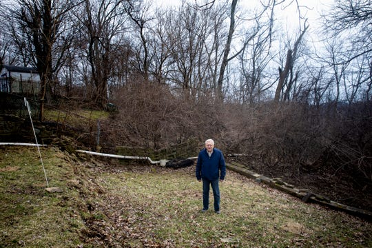 Tom Gerrein stands in his backyard in Bellevue, Kentucky, Tuesday, February 19, 2019. He and his wife moved into their home in the summer of 1969. On Easter morning in 2010, they came home from church to find a landslide they have since learned is affecting more than 35 properties in Bellevue.