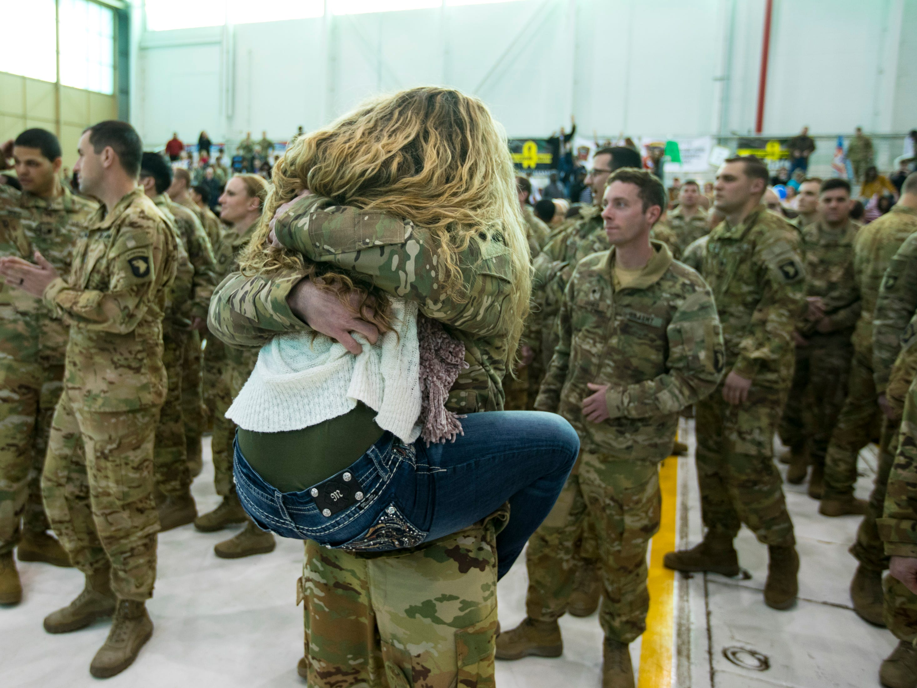 A woman jumps on a soldier during a homecoming ceremony for members of the 101st Combat Aviation Brigade and 101st Sustainment Brigade at Fort Campbell in Clarksville on Thursday, Feb. 21, 2019. The soldiers were returning from a nine-month deployment to Afghanistan.
