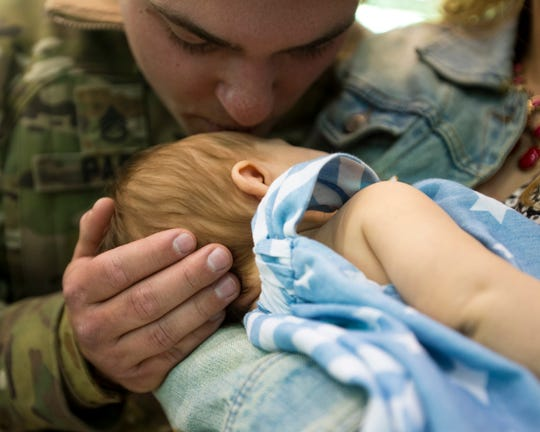 Staff Sgt. R.J. Paski kisses his daughter Gianna Paski, 2 months, during a homecoming ceremony for members of the 101st Combat Aviation Brigade and 101st Sustainment Brigade at Fort Campbell in Clarksville on Thursday, Feb. 21, 2019. It was the first time Staff Sgt. Paski met his daughter. The soldiers were returning from a nine-month deployment to Afghanistan.