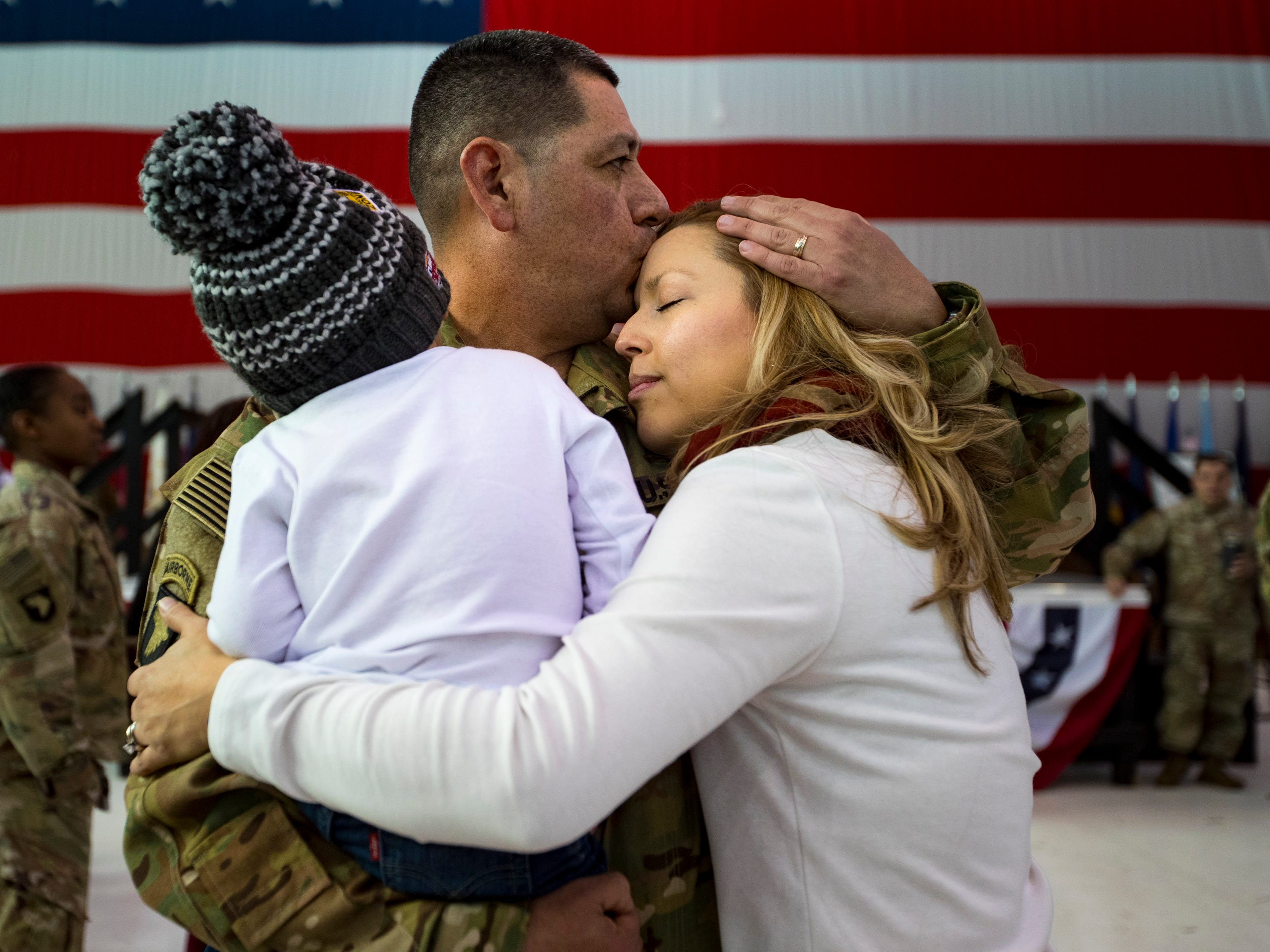 Gustavo Canales kisses Scarleth Canales while holding Raul Canales, 3, during a homecoming ceremony for members of the 101st Combat Aviation Brigade and 101st Sustainment Brigade at Fort Campbell in Clarksville on Thursday, Feb. 21, 2019. The soldiers were returning from a nine-month deployment to Afghanistan.