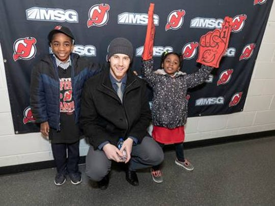 New Jersey Devils Defenseman Damon Severson, #28, signed memorabilia during a meet-and-greet with Sammie and his sister, Priscilla, after the game.