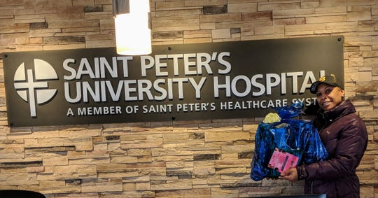 "YQ Dreams Entertainment CEO Quana Fladger delivering dolls collected through her ""Q's Dolls for Daughters"" charity initiative to Saint Peter's University Hospital in New Brunswick"