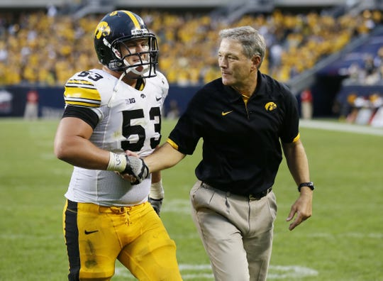 Iowa head coach Kirk Ferentz congratulates his son James after Iowa's win over Northern Illinois at  Soldier Field in Chicago on Saturday, Sept. 1, 2012.