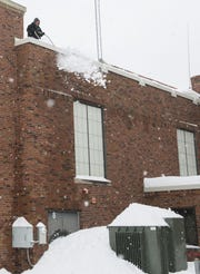 A Service Roofing worker shovels snow off the roof of Lowell Elementary School in Waterloo, Iowa, on Wednesday, Feb. 20, 2019, after part of the roof collapsed.