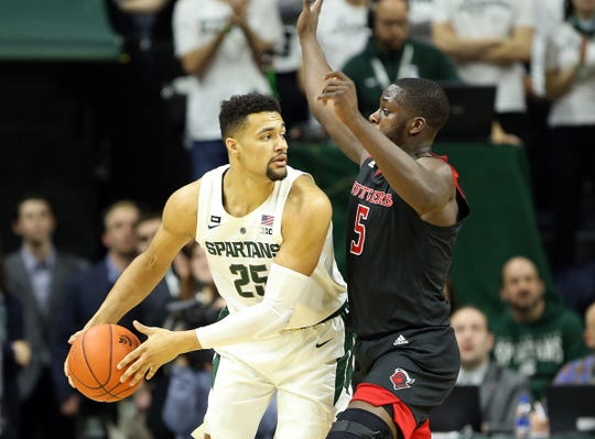 Michigan State Spartans forward Kenny Goins (25) is defended by Rutgers Scarlet Knights forward Eugene Omoruyi (5) during the first half of a game at the Breslin Center on Feb. 20, 2019.