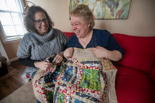 """Courtney Wooten, 49, of Berkley left, gives a quilt to Tammy Phillips, 54, of Berkley. Wooten, an administrator for the Berkley Buy Nothing Facebook Group, posted the quilt her aunt made to the site and Phillips thought it would make a great gift for her nephew and his wife who are expecting their first child in August. """"That's what makes this great,"""" Wooten said. """"Now, Tammy and I know one another."""""""