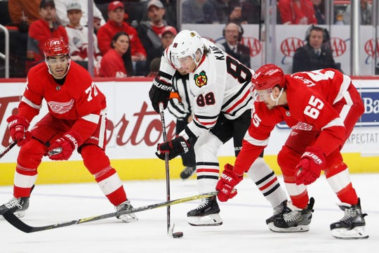 Chicago Blackhawks right wing Patrick Kane (88) goes up against Detroit Red Wings defenseman Danny DeKeyser (65) and center Andreas Athanasiou (72) during the first period at Little Caesars Arena on Feb. 20, 2019.