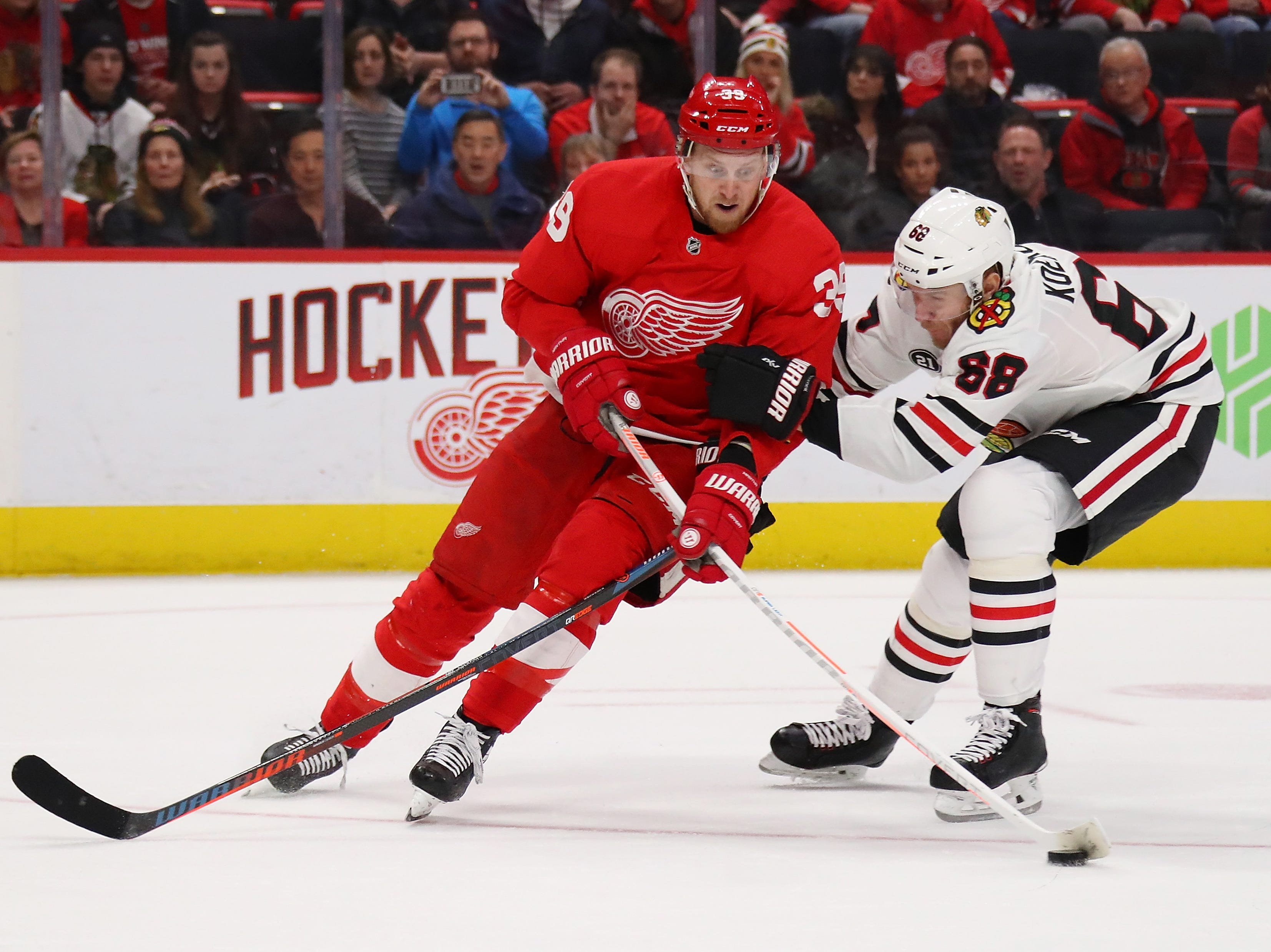 Red Wings forward Anthony Mantha tries to get a shot off next to Blackhawks defenseman Slater Koekkoek during overtime of the Wings' 5-4 loss on Wednesday, Feb. 20, 2019, at Little Caesars Arena.