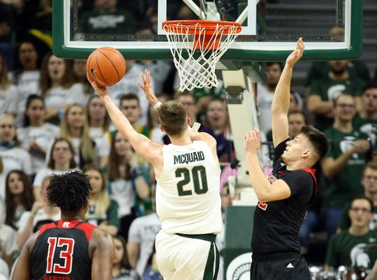 Michigan State Spartans guard Matt McQuaid (20) drives to the basket in front of Rutgers Scarlet Knights guard Caleb McConnell (22) during the first half of a game at the Breslin Center on Feb. 20, 2019.