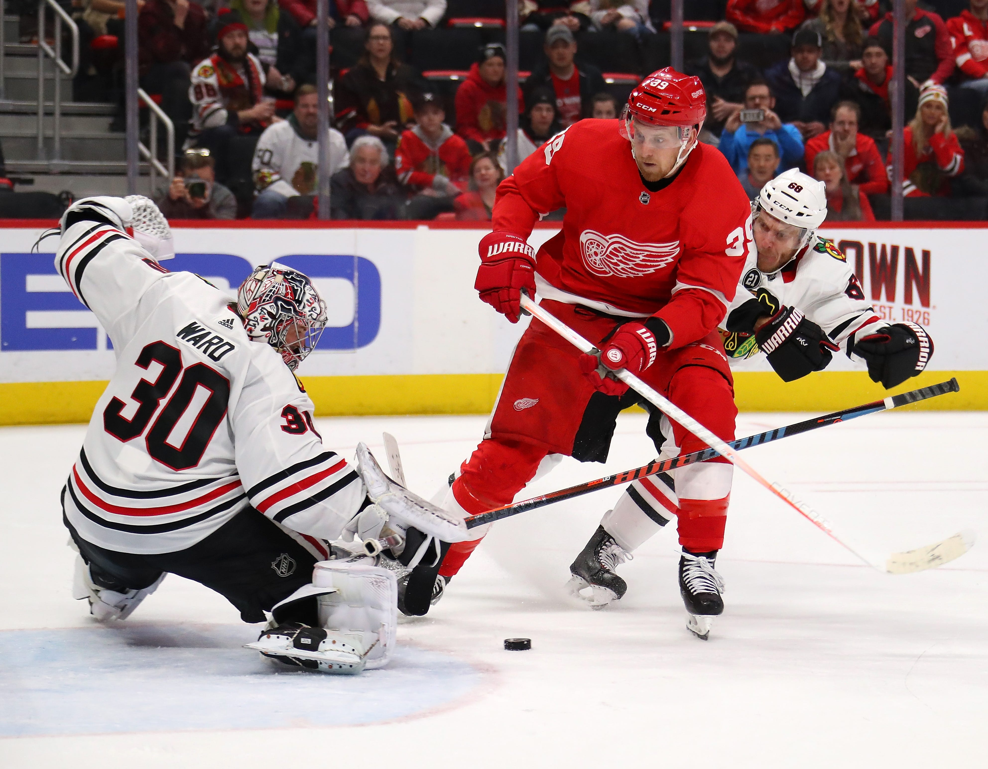 Red Wings forward Anthony Mantha tries to get a shot off between Blackhawks goalie Cam Ward and defenseman Slater Koekkoek during overtime of the Wings' 5-4 loss on Wednesday, Feb. 20, 2019, at Little Caesars Arena.