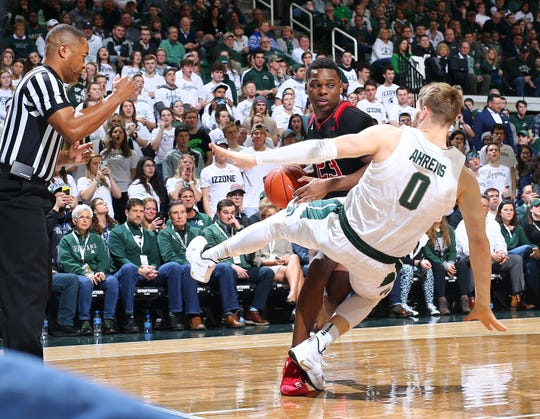 Montez Mathis  #23 of the Rutgers Scarlet Knights drives to the basket and draws a foul from Kyle Ahrens #0 of the Michigan State Spartans in the second half at Breslin Center on February 20, 2019 in East Lansing, Michigan.